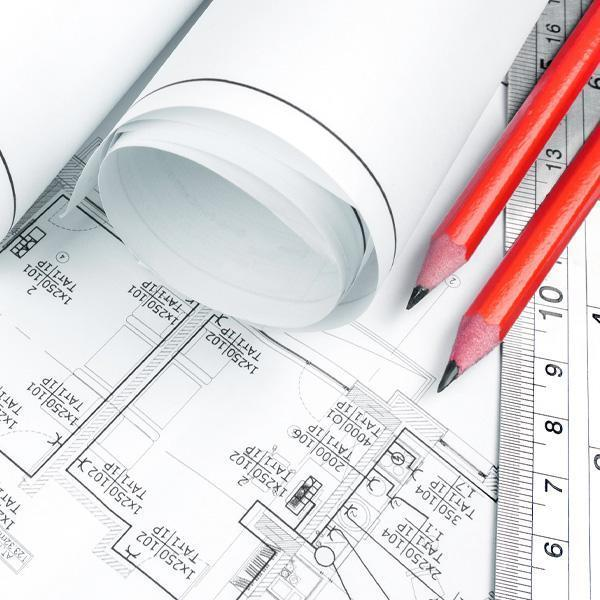 linijka ołówki zwinięte plany leżą narozłożonych planach